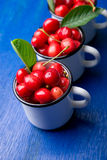 Cherry in enamel cup on blue wooden background. Healthy, summer fruit. Cherries. Royalty Free Stock Photography