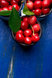 Cherry in enamel cup on blue wooden background. Healthy, summer fruit. Cherries. Top view. Copy space. Stock Images