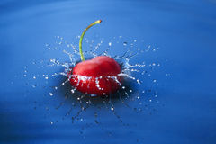 Cherry falls in water. Cherry falls deeply under water with a splash Stock Photos