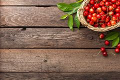 Cherry. Fresh sweet cherry with leaves in basket on wooden table Royalty Free Stock Photography