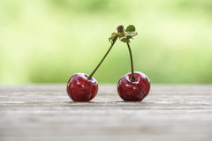 Cherry fruit on wooden table over bokeh green background royalty free stock photos