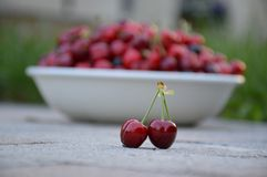 Two cherry fruit on many cherry in the bowl background royalty free stock images