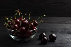 Cherry in a glass plate on a black wooden background Stock Images