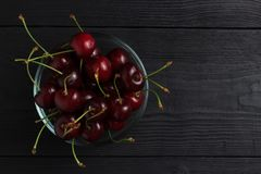 Cherry in a glass plate top view on a black wooden background Royalty Free Stock Photo
