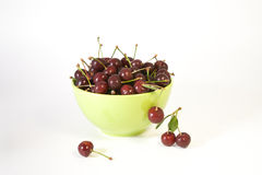 Cherry in the green bowl. On the white background Stock Photo