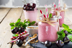 Cherry healthy smoothie with granola and berries. Stock Image