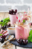 Cherry healthy smoothie with granola and berries. Stock Photos
