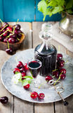 Cherry homemade liquor in a vintage bottle with fresh cherries. Royalty Free Stock Photography
