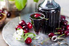 Cherry homemade liquor in a vintage bottle with fresh cherries. stock photo