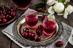 Cherry homemade liquor in a vintage glasses on metal tray and cherries. stock images