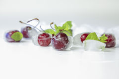 Cherry in ice cube with mint leaves Royalty Free Stock Photography