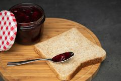 Cherry jam with berries in a glass jar with an open red and white lid next. Next to a wholegrain toast with an empty teaspoon. On stock photo