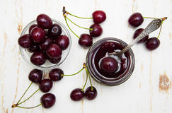 Cherry jam. With fresh cherries on a wooden background stock photo
