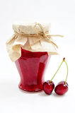 Cherry jam and fruits. Jar of homemade cherry jam and couple of cherries Royalty Free Stock Photo