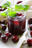 Cherry jam in a glass jar and ripe berries Stock Photo