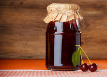 Cherry jam jar on dishcloth Stock Image