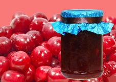 Cherry jam jar on a ripe berries background. Royalty Free Stock Images