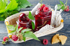 Cherry jam and raspberry. In glass jars on wooden table Stock Photo