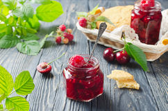 Cherry jam and raspberry. In glass jars on wooden table Stock Image