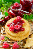 Cherry jam and raspberry. In glass jars on wooden table Royalty Free Stock Photography