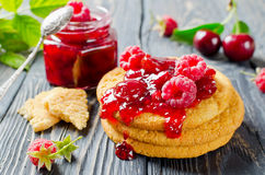 Cherry jam and raspberry. In glass jars on wooden table Royalty Free Stock Photos