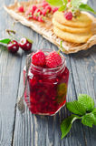 Cherry jam and raspberry. In glass jars on wooden table Stock Images
