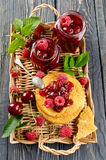 Cherry jam and raspberry. In glass jars on wooden table Royalty Free Stock Photo