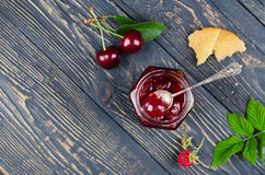 Cherry jam and raspberry. In glass jars on wooden table. Top view Stock Images