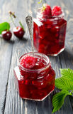 Cherry jam and raspberry on a rustic wooden table. Cherry jam and raspberry in glass jars on wooden table Stock Photography