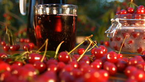 Cherry juice on the background of growing cherries. Slow motion. The smooth glide of the camera  from right to left  along the table with a cherries and juice stock footage