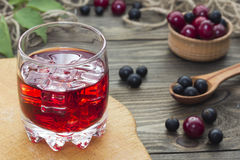 Cherry juice , cherries and currants in a wooden spoon Stock Photography