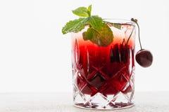 Cherry Juice en un vidrio con la menta y las cerezas frescas se cierran para arriba en el fondo blanco, espacio de la copia foto de archivo