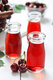 Cherry juice. In jars and fresh ripe cherries on wooden background Stock Photo