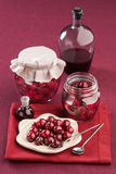 Cherry in juice in the pot. On a red napkin Royalty Free Stock Images