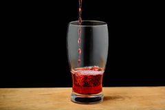 Cherry juice pouring into glass on wooden desk. Stock Photo