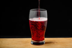 Cherry juice pouring into glass on wooden desk. Royalty Free Stock Images