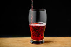 Cherry juice pouring into glass on wooden desk. Royalty Free Stock Photos