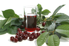 Cherry juice and red cherries. Cherry juice in a glass and some red cherries Royalty Free Stock Photography