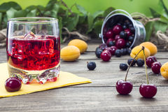 Cherry juice. Stands on a wooden table with berries Royalty Free Stock Photos