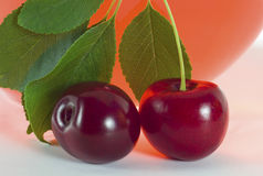 Cherry. Juicy red cherries with green leaves on a background vessel with cherry drink Royalty Free Stock Photo