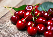 Cherry with leaf. On wood background Royalty Free Stock Images