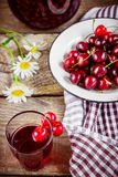 Cherry lemonade and flowers on wooden background. Stock Images