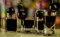 Cherry liqueur and juicy ripe cherries on the table in the bar, royalty free stock image