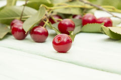 Cherry lying on a wooden surface. Beautiful bright red, ripe, cherry lie on a wooden surface near the branches and leaves of the tree cherry Royalty Free Stock Photos