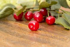Cherry lying on a wooden surface. Beautiful bright red, ripe, cherry lie on a wooden surface near the branches and leaves of the tree cherry Royalty Free Stock Photo
