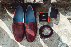 Cherry men`s shoes, belt and wedding rings in a box. groom`s accessories at the wedding day Stock Image