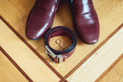 Cherry men`s shoes, belt and wedding rings in a box. groom`s accessories at the wedding day Royalty Free Stock Image