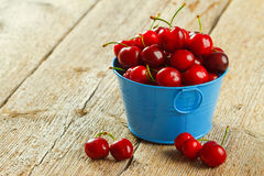 Cherry. In metalic bowl isolated on wooden background Royalty Free Stock Photo