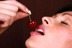 Cherry mouth. Red cherry eating brunette with lipstick stock photo