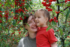 The Cherry Orchard. Mother and daughter among the ripe berries of cherry in the garden Royalty Free Stock Photos